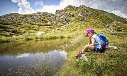 Girl having a break from hiking sitting at a mountain lake, Passeier Valley, South Tyrol, Italy - DIKF00340
