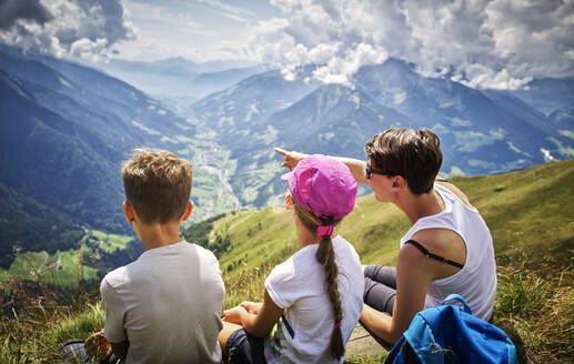 Mother with two children having a break from hiking in alpine scenery, Passeier Valley, South Tyrol, Italy - DIKF00343