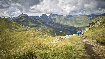 Mother with two children hiking in alpine scenery, Passeier Valley, South Tyrol, Italy - DIKF00346