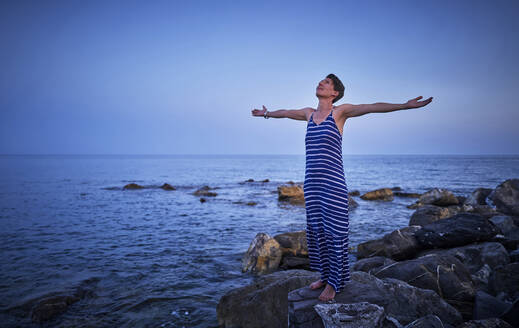 Happy mature woman standing barefoot on rocks in front of the sea looking up, Italy - DIKF00348