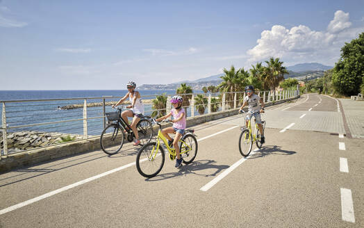 Mother with children during bicycle tour between San Lorenzo and San Remo, Italy - DIKF00351