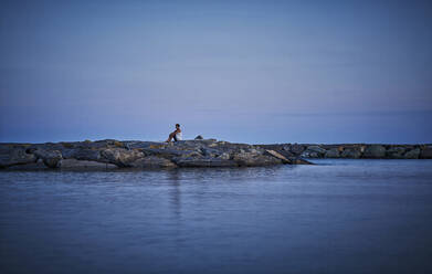 Mature woman sitting at port entrance  at twilight looking at distance, Italy - DIKF00357