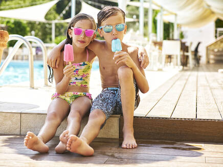 Portrait of little girl and boy with popsicles wearing mirrored sunglasses in front of swimming pool - DIKF00360