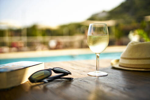 Glass  of cooles white wine, book, sunglasses and straw hat in  front of swimming pool, Italy - DIKF00366