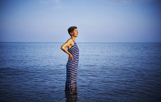 Mature woman standing in the sea watching sunset, Italy - DIKF00369