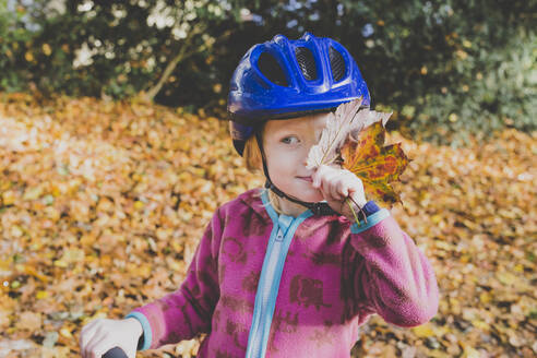Portrait of little girl with autumn leaves wearing blue cycling helmet - IHF00222
