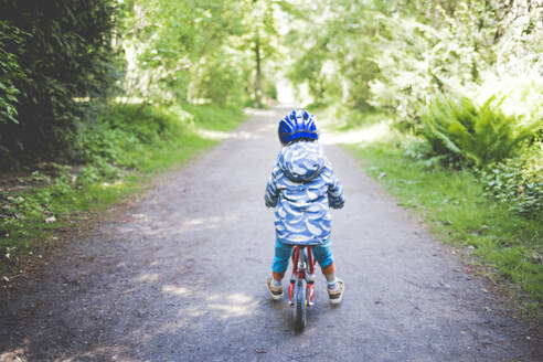 Back view of toddler girl with blue cycling helmet on bogie wheel - IHF00249