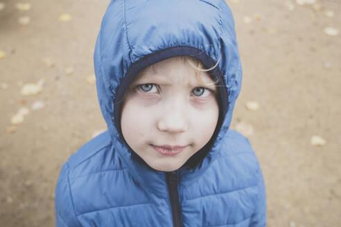 Portrait of grumpy little boy wearing blue anorak - IHF00255