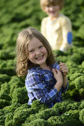 Smiling girl and boy in a kali field - ECPF00784