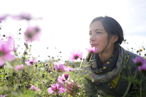 Portrait of women smelling on wild flower, flower meadow - ECPF00790