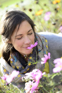 Portrait of women smelling on wild flower, flower meadow - ECPF00793