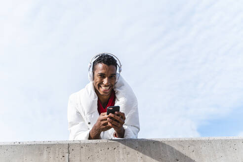 Portrait of happy young man with headphones and smartphone outdoors - AFVF04648