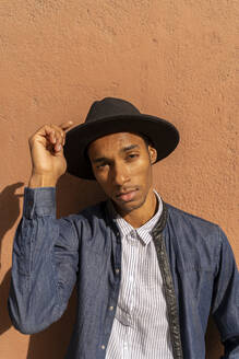 Portrait of stylish young man wearing a hat at a wall - AFVF04684