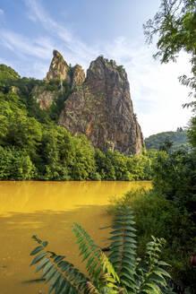 Germany, Rhineland-Palatinate, Bad Munster am Stein-Ebernburg, Yellow Nahe river with Rheingrafenstein rock formation in background - PUF01749