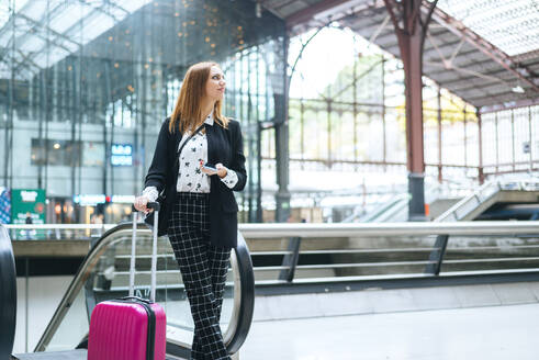 Young woman with suitcase and cell phone at train station - KIJF02862