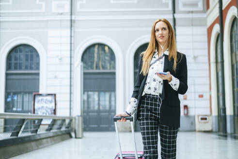 Young woman with suitcase, earphones and cell phone on the go at train station - KIJF02868