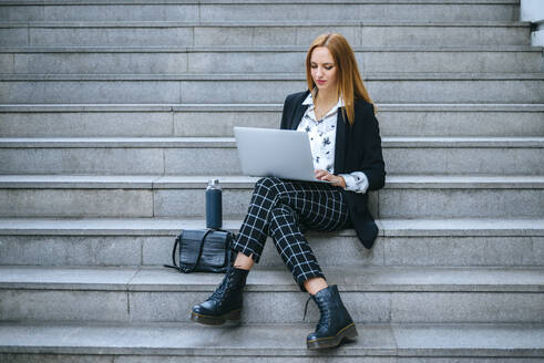 Young businesswoman sitting on stairs using laptop - KIJF02871