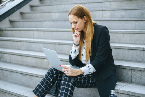 Young businesswoman sitting on stairs using laptop - KIJF02877