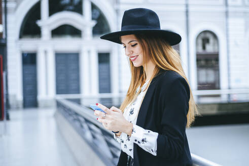Smiling young woman wearing a hat using cell phone at train station - KIJF02886