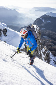 Alpinist ascending a snowy mountain, Orobie Alps, Lecco, Italy - MCVF00153