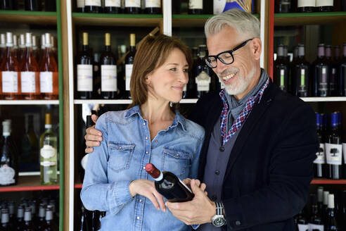 Mature couple choosing bottle of wine at a wine shop - ECPF00847