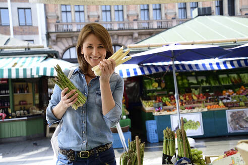 Portrait of smiling mature woman choosing asparagus at a market stall - ECPF00856