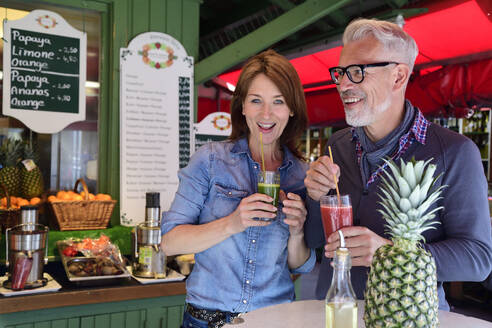 Portrait of happy mature couple drinking a healthy juice at a market stall - ECPF00862