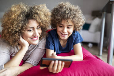 Mother and son watching a video on smartphone, lying on big pillow - FMKF06069