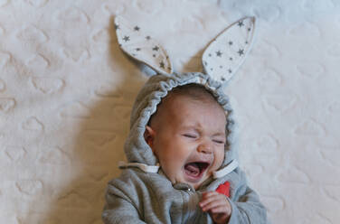 Portrait of crying baby girl in a rabbit hoodie lying on white blanket - GEMF03380