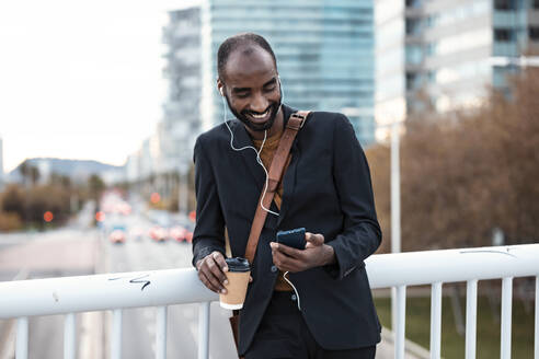 Smiling young businessman with coffee to go listening music with earphones and smartphone - JSRF00690