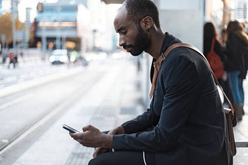 Young businessman sitting at tram stop looking at smartphone - JSRF00702