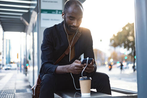 Young businessman sitting at tram stop in the evening using earphones and smartphone - JSRF00708