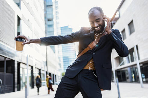 Portrait of happy young businessman dancing on the street while listening music with earphones - JSRF00714