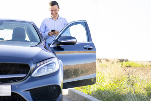 Smiling young businessman using smartphone at car on country road - CJMF00218