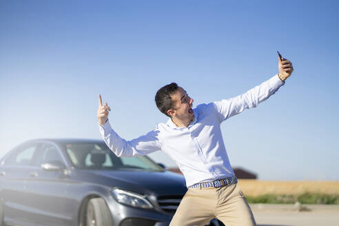 Carefree young businessman taking a selfie next to car on country road - CJMF00224