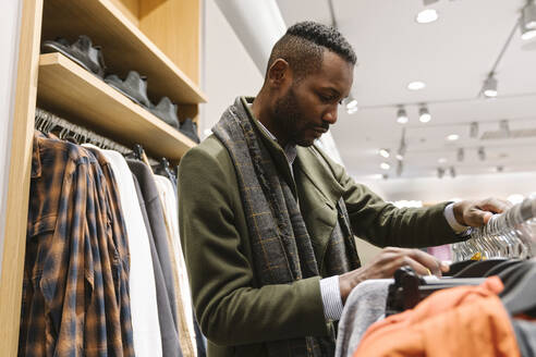 Stylish man shopping in a clothes store - AHSF01641