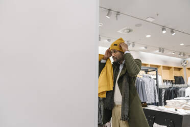 Stylish man shopping in a clothes store trying on a beanie - AHSF01644