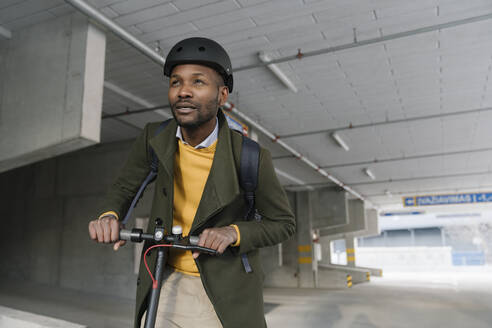 Portrait of stylish man with helmet and scooter in the city - AHSF01662