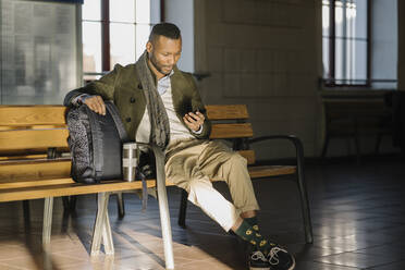 Stylish man using smartphone while sitting on a bench in a train station - AHSF01677