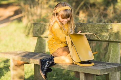 Little blond girl dressed in yellow sitting on garden bench with leather bag - NMSF00382