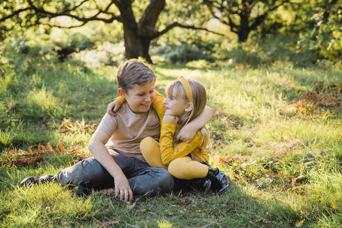 Portrait of happy little girl arm in arm with her older brother on a meadow - NMSF00397
