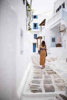 Woman walking through narrow lanes of Mykonos, Greece - DAWF00981