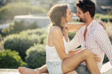 Romantic couple sitting on wall, embracing, enjoying holidays - DAWF00987