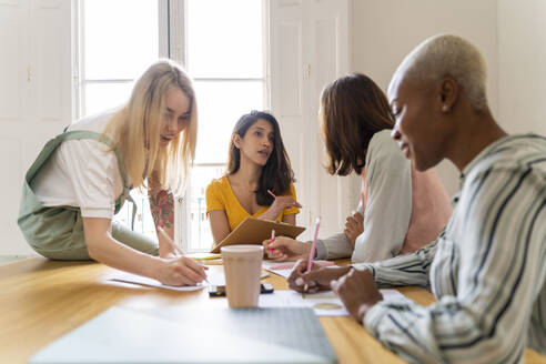 Businesswomen having a meeting and taking notes in office - AFVF04718