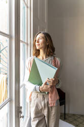 Woman holding folder looking out of window - AFVF04736