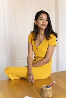 Businesswoman having a break sitting on table in office - AFVF04751