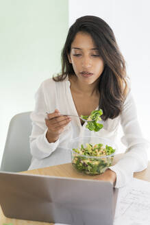 Portrait of young architect eating mixed salad at desk looking at laptop - AFVF04772