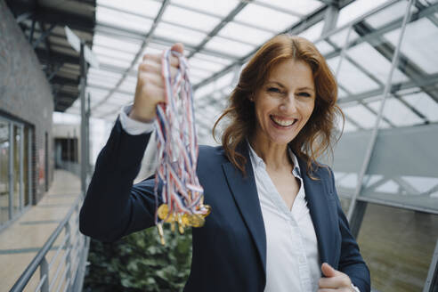Portait of a happy businesswoman holding medals in office - JOSF04147