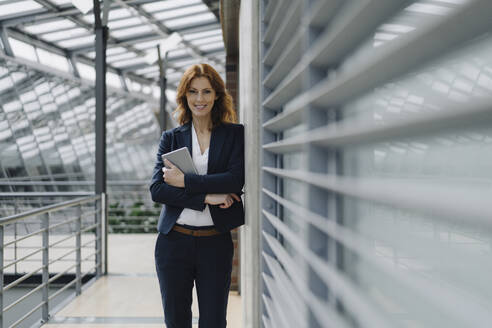 Portrait of a smiling businesswoman holding a tablet in a modern office building - JOSF04153