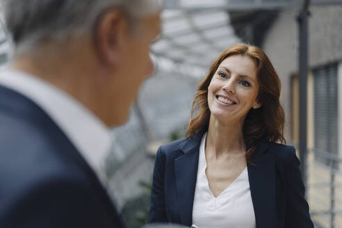 Portrait of smiling businesswoman talking to businessman in office - JOSF04159